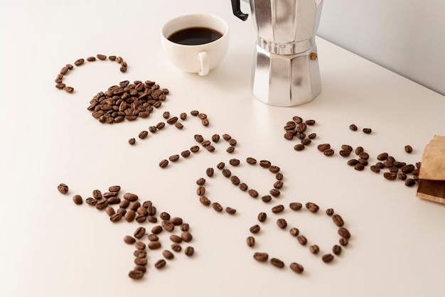 Café écrit avec des grains de café sur un tableau blanc