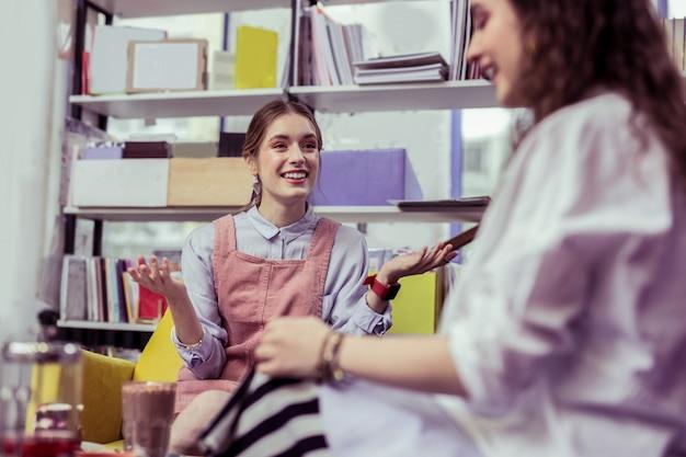Café élégant. fille aux cheveux clairs souriante, écartant ses mains lors de la discussion avec un ami rayonnant