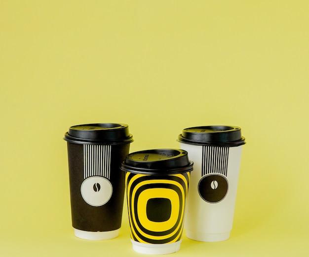 Café à emporter en tasse thermo sur fond jaune.