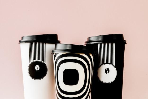 Café à emporter en tasse thermo sur fond rose.