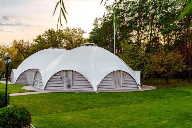 Café d'été avec tente en tissu sur le toit en forme de dôme avec portes d'entrée en bois. lieu de vacances d'été