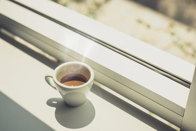 Café expresso chaud posé sur une table près de la fenêtre