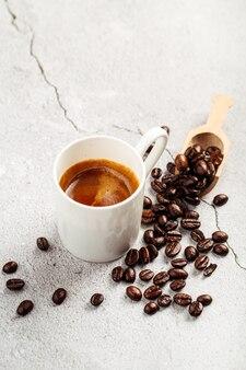 Café expresso dans une tasse blanche sur fond de béton décoré de haricots