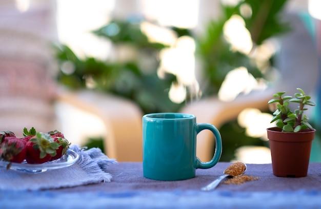 Café expresso dans une tasse en céramique turquoise en plein air sur balcon avec plantes et chaises