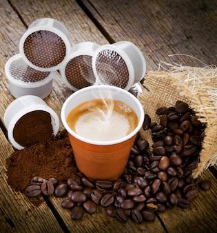 Café expresso dans une tasse jetable avec des gousses