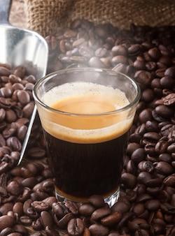 Café expresso dans une tasse en verre avec grains de café.