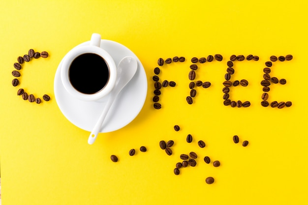 Café expresso en petite tasse en céramique blanche avec grains de café et mot café
