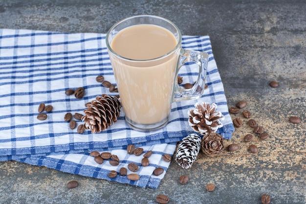 Café expresso avec pommes de pin et grains de café sur nappe. photo de haute qualité