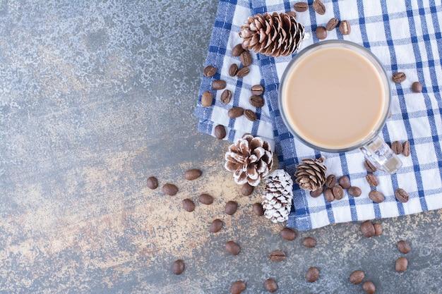 Café expresso avec des pommes de pin et des grains de café sur une nappe.