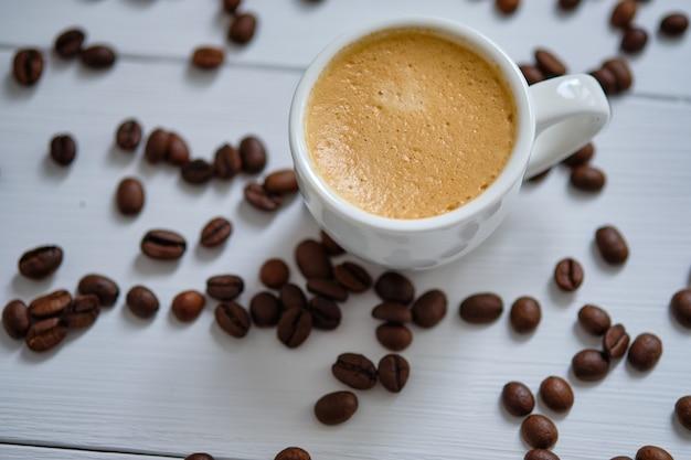 Café expresso sur une table en bois blanc avec des grains de café.