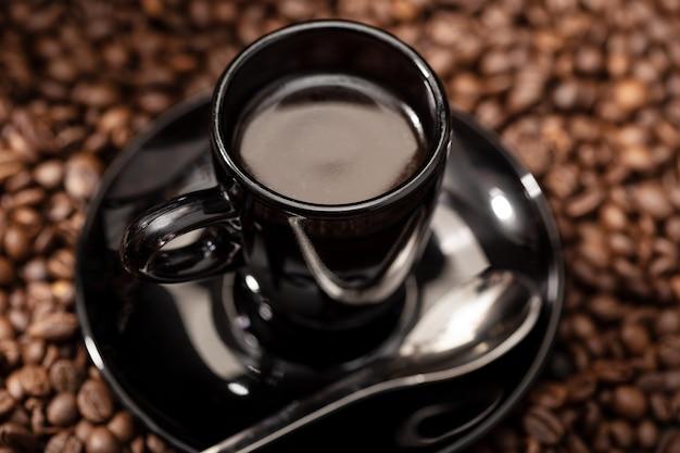 Café expresso en tasse noire et grains torréfiés. fond de café