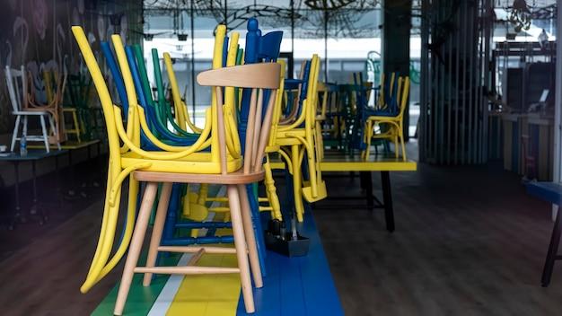 Café fermé avec chaises multicolores soulevées visibles à travers la façade en verre à bucarest, roumanie