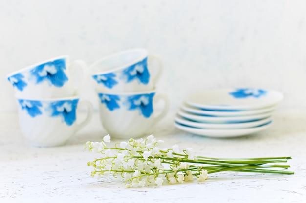 Café sur fond blanc et fleurs. lys de la vallée. printemps. matin. 8 mars. journée de la femme
