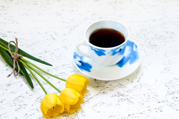 Café sur fond blanc et fleurs. tulipe. printemps. matin. 8 mars. journée de la femme