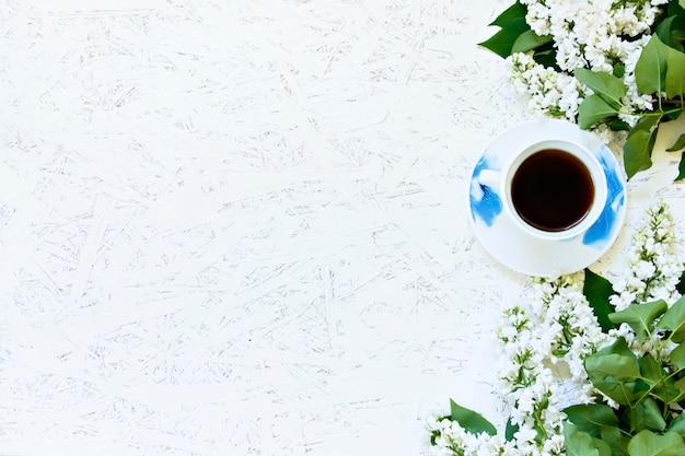 Café sur un fond en bois et des fleurs. lilas. printemps. matin. 8 mars. journée de la femme