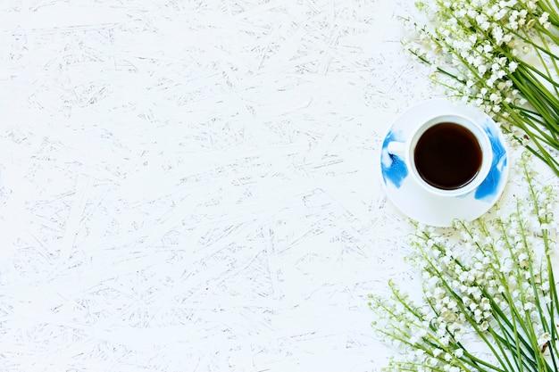 Café sur un fond en bois et des fleurs. lys de la vallée. printemps. matin. 8 mars. journée de la femme