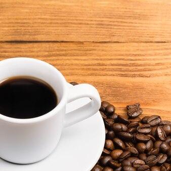 Café fraîchement préparé dans une tasse blanche entourée de grains de café