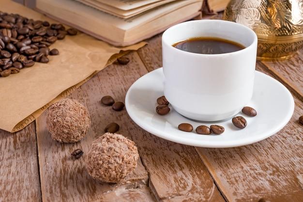 Café frais broyé dans la boisson du matin cezve dans une tasse blanche à côté de boules de chocolat