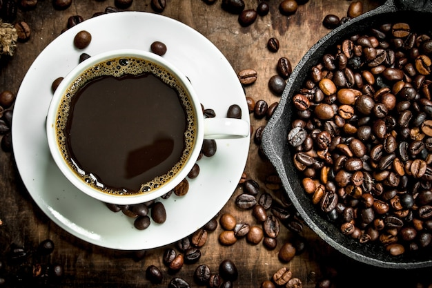 Café frais dans une tasse de café grillé sur une table en bois