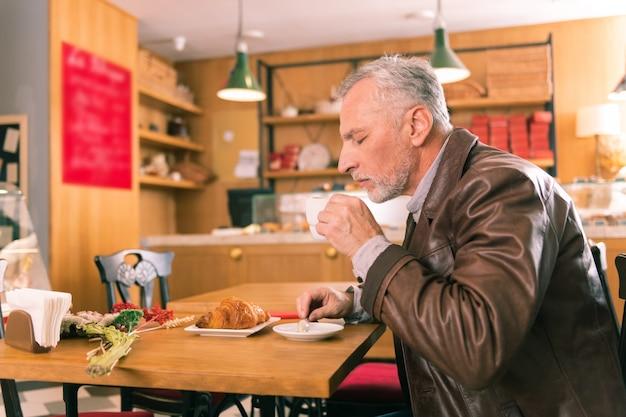 Café frais. homme d'âge mûr aux cheveux gris barbu se sentant tout simplement incroyable tasse de café frais