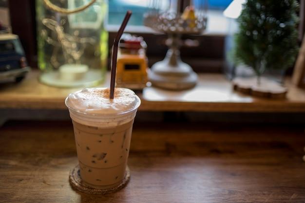Le café froid est placé sur la table en bois