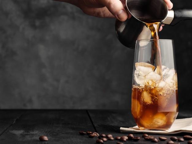 Le café froid est versé d'un turc dans un verre à whisky avec de la glace sur une table en bois gris. café glacé.