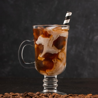 Café froid avec de la glace et de la crème dans un verre avec de la paille