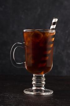 Café froid avec de la glace et de la paille dans un verre