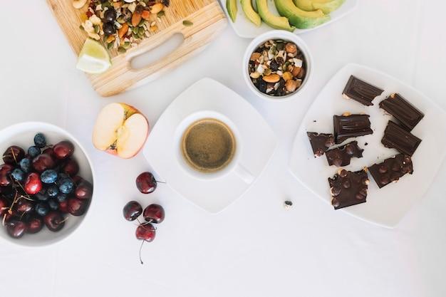 Café; fruit sec; morceaux de chocolat; cerise et fruits sur fond blanc