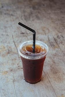 Café glacé americano noir sur le vieux bureau en bois