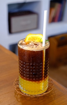 Café glacé americano yuzu sur table en bois