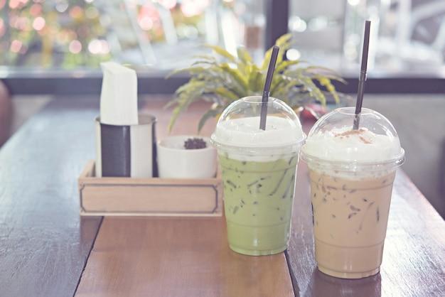 Café glacé au lait et thé vert glacé sur une table en bois dans un café.
