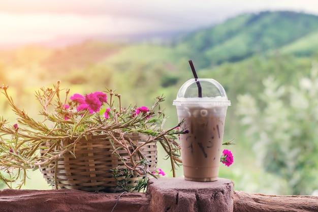 Café de glace closeup dans une tasse en plastique avec belle fleur sur fond de montagne