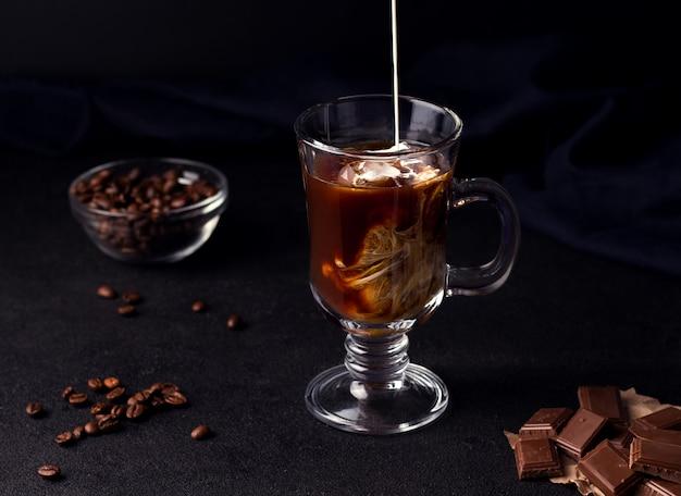 Café avec de la glace et de la crème sur fond noir à côté de grains de café et de chocolat