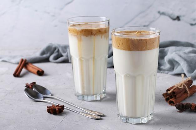 Café glacé dalgona dans de grands verres sur béton gris clair