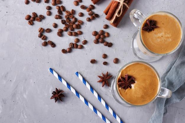Café glacé dalgona dans de grands verres avec des épices sur gris clair