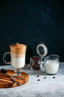 Café glacé dalgona dans un verre sur fond sombre