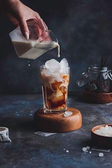 Café glacé dans un grand verre avec de la crème versée