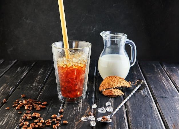Café glacé dans un style thaï avec du lait de coco et des grains de café sur un bois noir