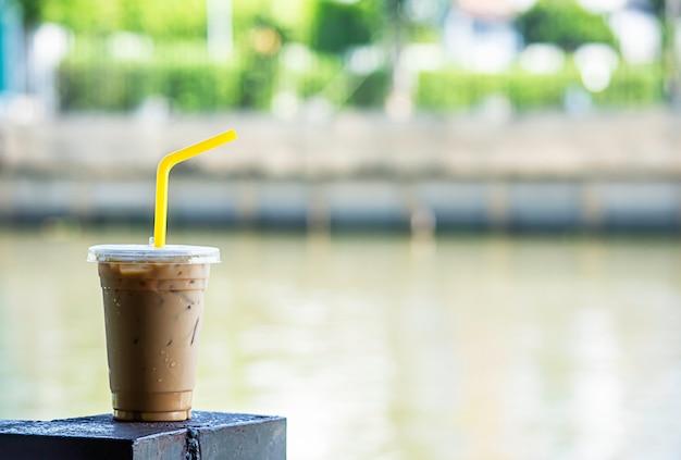 Café glacé dans un verre flou fond rivière.