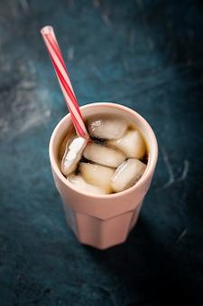 Café glacé dans un verre sur une surface de pierre bleu foncé. boisson rafraîchissante concept, soif, été, cola avec de la glace. mise à plat, vue de dessus