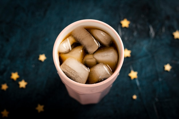 Café glacé dans un verre sur une surface de pierre bleu foncé avec des étoiles. mise à plat, vue de dessus