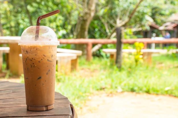 Café glacé dans un verre sur la table fond herbe et arbre.