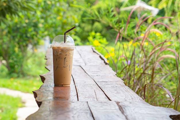 Café glacé dans un verre sur la table fond pennisetum pedicellatum et arbre.