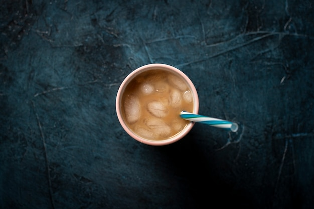 Café avec de la glace et du lait dans un verre sur un fond de pierre bleu foncé. boisson rafraîchissante concept, soif, été, glace, vie nocturne, club. mise à plat, vue de dessus