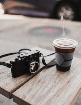 Café glacé à emporter et appareil photo vintage sur une table