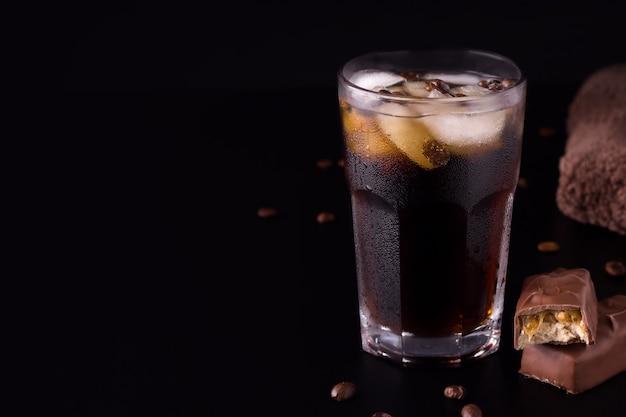 Café glacé sur fond noir, à côté d'une barre de chocolat