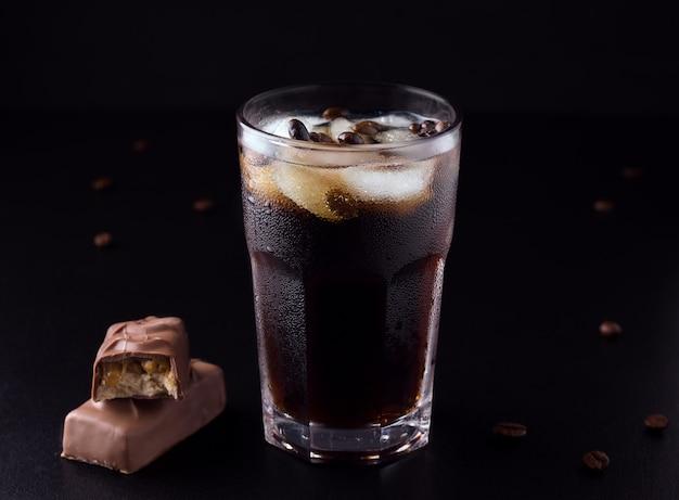 Café glacé sur fond noir à côté de grains de café avec une barre de chocolat