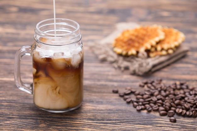 Café glacé et grains de café sur bois