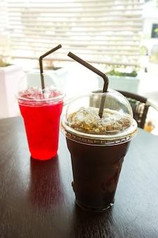 Café glacé et jus rouge dans une tasse en plastique. fond de nourriture et de boisson.